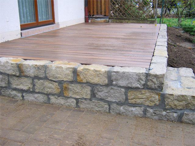 Terasse aus Holzbohlen, erhöht und eingafasst mit Naturstein