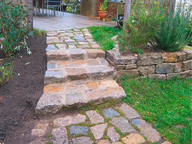 Terrassenanlage mit Natursteintreppe, sichtbar ist der Übergang zur Terrasse mit Garten, eingefasst mit Sträuchern und Rasen